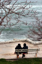 Couple of women sitting on the bench in front of the cold winter Royalty Free Stock Photo