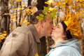 Couple with wreath of leaves kissing in forest Royalty Free Stock Image