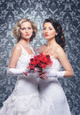 A couple of young and attractive brides in white clothes caucasian posing holding bouquet red flowers the image is taken Royalty Free Stock Image