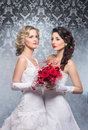 A couple of young and attractive brides in white clothes caucasian posing holding bouquet red flowers the image is taken Royalty Free Stock Photo