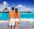 Couple of young tourists in a tropical beach summer rear view hug Stock Photo