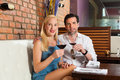 Couples attrayants buvant du vin rouge dans le bar Photographie stock