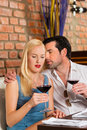 Couples attrayants buvant du vin rouge dans le restaurant Photo libre de droits