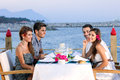 Couples celebrating at a seaside restaurant two attractive young sitting table the waters edge waiting for their meal and Stock Photography