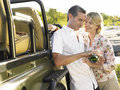 Couples heureux par jeep with wine Photos stock