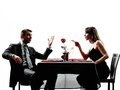 Couples lovers dating dinner dispute arguing dinning in silhouettes on white background Royalty Free Stock Photos