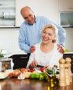 Couples m rs heureux faisant cuire la soupe végétarienne Photographie stock