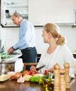 Couples pluss âgé affectueux faisant les travaux domestiques et faisant cuire ensemble Photographie stock libre de droits