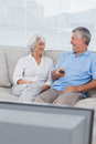 Couples regardant la tv sur le divan Images stock