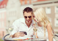 Couples regardant le smartphone en café Image stock