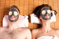 Couples retreat facial mask spa holiday at getting with cucumber skincare relaxing beauty treatment on bamboo Stock Image