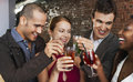 Couples toasting drinks at bar two happy multiethnic the Royalty Free Stock Images