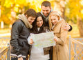 Couples with tourist map in autumn park holidays and tourism concept group of friends or Royalty Free Stock Photo