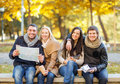 Couples with tourist map in autumn park holidays and tourism concept group of friends or Stock Photos