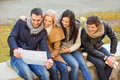 Couples with tourist map in autumn park holidays and tourism concept group of friends or Stock Photography