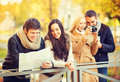 Couples with tourist map and camera in autumn park holidays tourism concept group of friends or Royalty Free Stock Photo