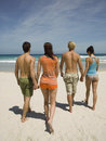 Couples walking on the beach towards sea Stock Image