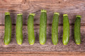 Courgettes a row of fresh on an old wood table Stock Image