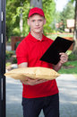 Courier bringing a package handsome young vertical Royalty Free Stock Photos