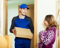 Courier brought package to woman smiling women at home Stock Photography