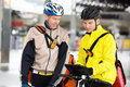 Courier delivery men two young in protective gear with bicycles using digital tablet Royalty Free Stock Photos