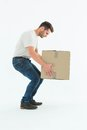 Courier man picking up cardboard box full length side view of on white background Stock Image