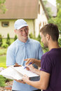 Courier and man signing a delivery form Royalty Free Stock Photo