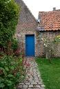 Courtyard garden with blue door at 15th century Jerusalem Church Jeruzalemkerk, Bruges / Brugge, Belgium. Royalty Free Stock Photo