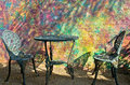 Courtyard table and chairs iron two found in a in front of a colorful painted wall Stock Photos