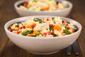 Couscous with chicken bean carrot and bell pepper two bowls of dish green red selective focus focus on the meat in the Royalty Free Stock Images