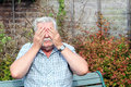 Covering eyes with hands an elderly man his both so that he can not see Royalty Free Stock Images