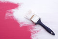Covering pink paint with a coat of white emulsion on wooden board paintbrush Stock Photos
