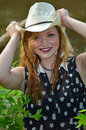 Cow girl de sourire heureuse mettant sur son cowboy hat Images libres de droits