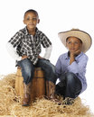 Cowboy brothers two elementary together one sitting on a barrel the other kneeling beside it in the hay on a white background Royalty Free Stock Photos