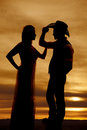 Cowboy couple stand silhouette his hand on hat a of a women reaching up to touch her cowboys arm Royalty Free Stock Images