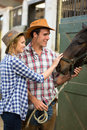 Cowboy cowgirl stable caring and in touching a horse Stock Photo