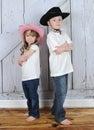 Cowboy et cow-girl d'enfant de mêmes parents dans la pose douce Image stock