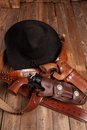 Cowboy gear hat revolvers and holsters on a wooden background Stock Image