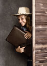 Cowboy girl or pretty woman in stylish hat and blue plaid shirt holding gun and old suitcase Royalty Free Stock Photo