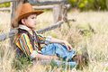 Cowboy on a grass at an old fence Royalty Free Stock Photo
