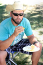 Cowboy at picnic a bearded with sunglasses and western hat sitting on stool eating a in a park shallow depth of field Royalty Free Stock Photography