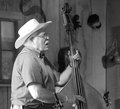 Cowboy plays bass instrument black and white middle aged playing a stringed in a barn country music festival Royalty Free Stock Images