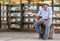 Cowboy seated on a farm Royalty Free Stock Photography