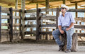 Cowboy seated on a farm Royalty Free Stock Image