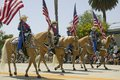 Cowboys marching with American Flags displayed during opening day parade down State Street, Santa Barbara, CA, Old Spanish Days Fi Royalty Free Stock Photo