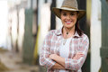 Cowgirl with arms crossed attractive inside stable Royalty Free Stock Photos