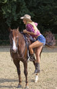 Cowgirl climbing on horse beautiful blond woman pulling herself the Stock Photo