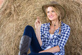 Cowgirl daydreaming beautiful sitting on hay and Stock Images