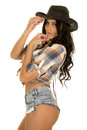 Cowgirl short denim shorts in hat hands by face Royalty Free Stock Photo
