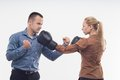 Coworkers in boxing gloves young attractive business women attacking men with fists isolated on white background Stock Photos